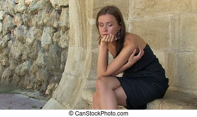 Beautiful young Woman sitting on stone bench