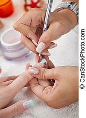Applying gel - Beautician applying gel on fingernails...