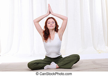 Young girl doing yoga exercises on sitting on the floor