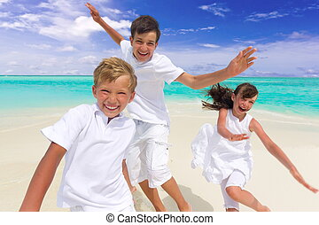 Happy children on beach - Three happy young children running...