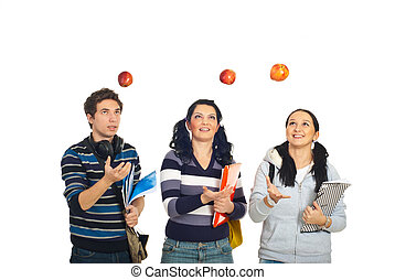 Students throw up apples - Three cheerful students throw up...