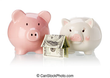 Pair of piggy banks with money house on white background