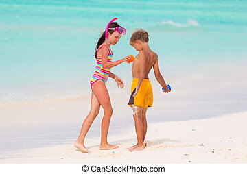 Children playing on beach - Young brother and sister playing...