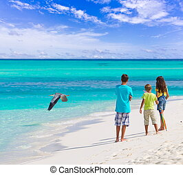 Children on beach - Three children watch a flying heron...