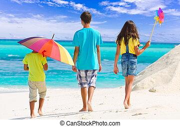 Three children on beach - Three children walking on a...