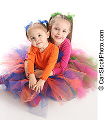 Sisters in bright tutu skirts - Two adorable sisters dressed...