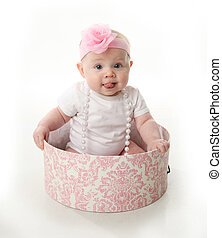 Pretty baby sitting in a hatbox - Portrait of an adorable...