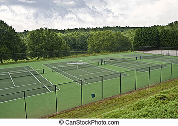 A Row of Empty Tennis Courts - Tennis courts that have been...