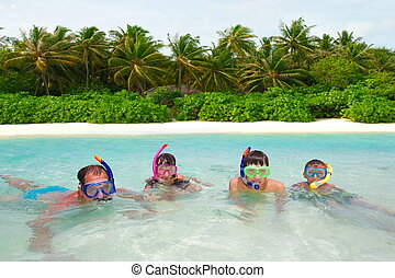 Family snorkeling in water