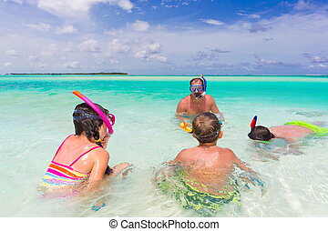 Family snorkeling in sea