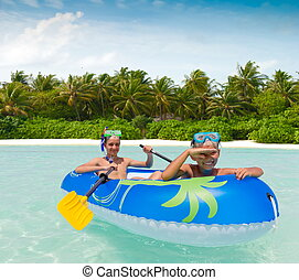 Children paddling rubber raft - Two children paddling a...