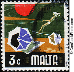 Girl water skiing - MALTA - CIRCA 1968: A stamp printed in...