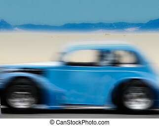 blue car driving fast on a desert road