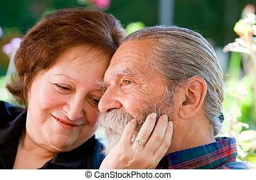 Old happy loving couple showing affection during retirement...