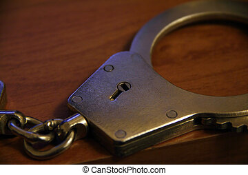 handcuff - closeup part of locked handcuffs with chain on...