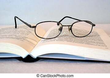 A pair of glasses and a book - A pair of eyeglasses and a...