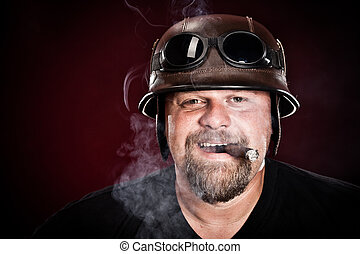biker in a helmet smokes a cigar on a dark background