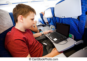 boy flies in the plane and plays the laptop