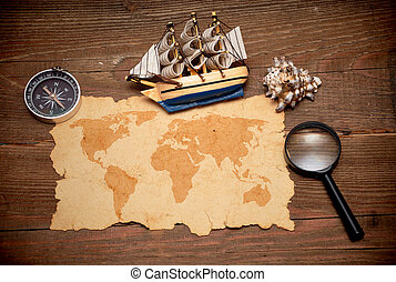 model classic boat, compass and loupe on wood background