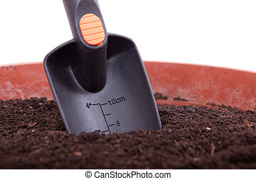 Measuring scoop in a flowerpot with soil