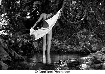 Getting dry - Naked woman towling off after swim in...