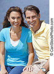 Portrait shot of an attractive, successful and happy middle aged man and woman couple in their thirties, sitting together outside and smiling.