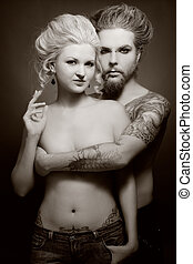 Gothic couple - Duotone shot of pierced tattooed man and...