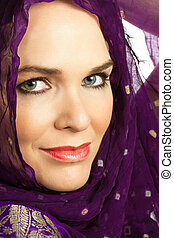 Closeup portrait of a beautiful Indian woman wearing a head scarf and looking at the camera