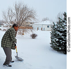 Winter snow. - African american male shoveling snow...