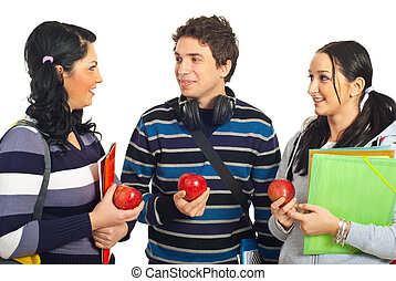 Students having conversation - Three students holding...