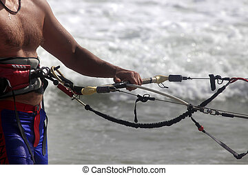 Kitesurfer with equipment on a coast of ocean