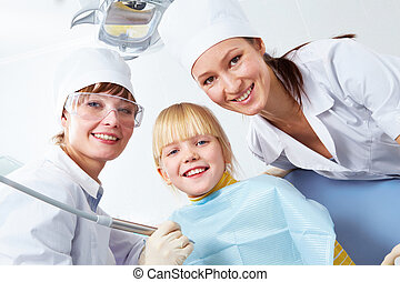 In dentists office - Group of dentist, assistant and little...