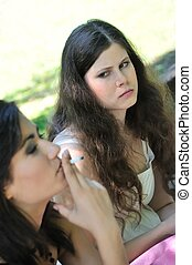 Young people outdoors - annoying by smoking cigarette -...