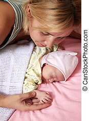 Mother with baby - Mother with her sleeping newborn baby in...