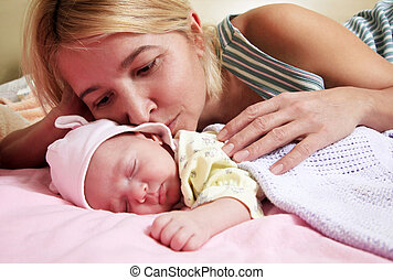 Mother with babe - Mother with her sleeping newborn baby in...