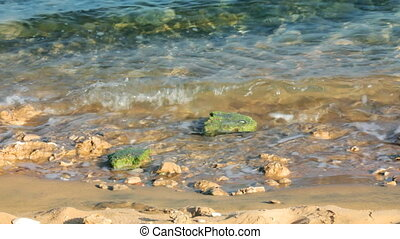 turquoise sea water waves and stones