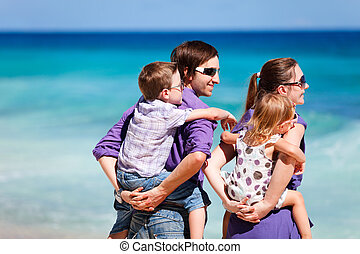 Family of four looking to ocean - Portrait of young parents...