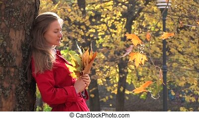 Young woman with maple leaves