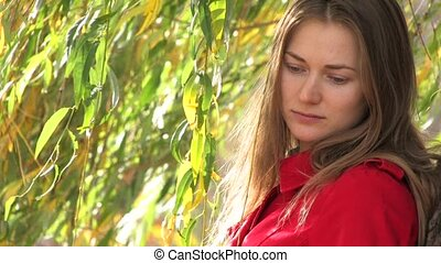 Thoughtful Young woman - Young woman in red coat, standing...