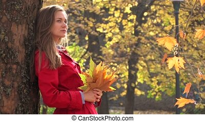 Young woman with autumn leaves - Young woman in red coat,...