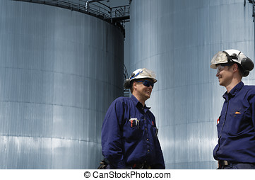 oil workers and fuel tanks - two oil workers in front of...