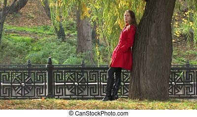 Young woman near tree in park - Young woman in red coat,...