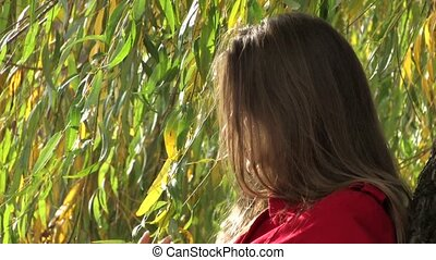 Young woman near willow tree II