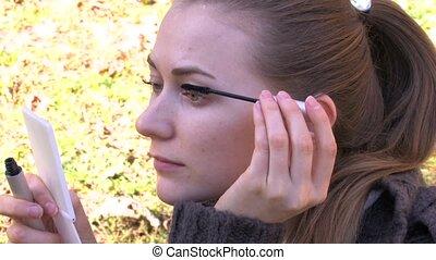 Young girl is doing eye makeup II