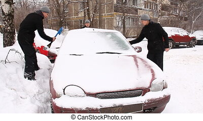 man cleans a car from the snow