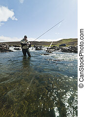 Caught one - Fly fisherman reeling in a salmon in beautiful...