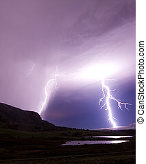 two lightning bolts reflecting in water - two lightning...