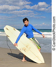 Surfer posing on the beach with his board