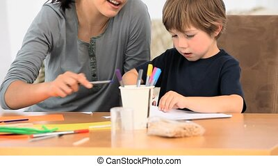 Boy drawing with his mother in the livingroom