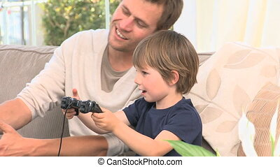 Son and dad playing video games in the livingroom